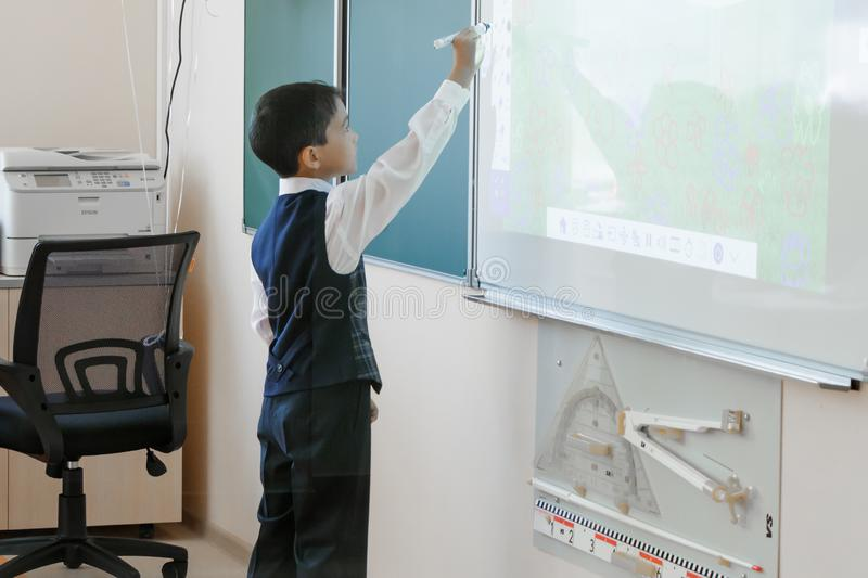 TyuSchool Stanza fredda Il ragazzo in uniforme scolastico scrive su una lavagna interattiva fotografie stock libere da diritti