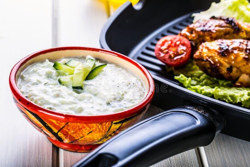 Tzatziki调味汁 Tzatziki选矿 穿戴与烤鸡腿的Tzatziki和新鲜蔬菜、莴苣叶子和樱桃tomatoe 免版税库存照片