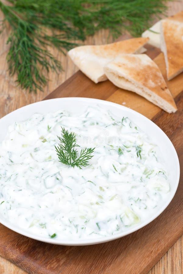 tzatziki σάλτσας γιαουρτιού με τα χορτάρια, αγγούρι και σκόρδο, κάθετα στοκ εικόνα
