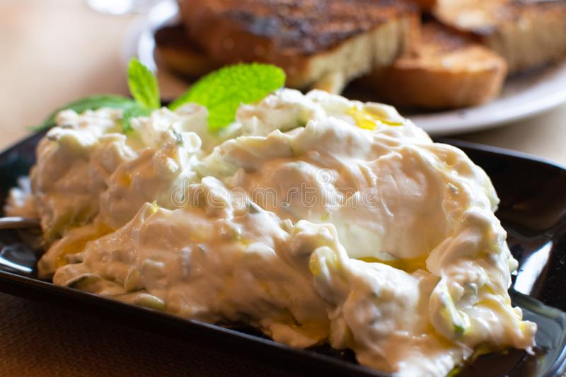 Tzatziki, cacik or tarator,  dip or sauce from Southeast Europe and Middle East made of salted strained yogurt mixed with. Cucumbers, garlic, salt, olive oil stock photography