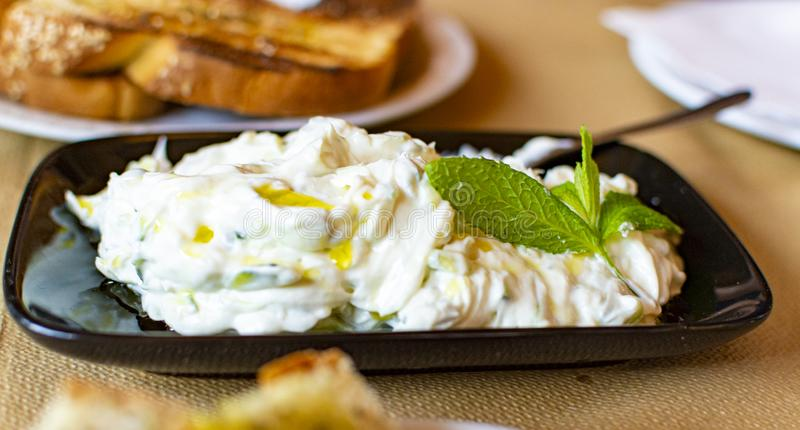 Tzatziki, cacik or tarator,  dip or sauce from Southeast Europe and Middle East made of salted strained yogurt mixed with. Cucumbers, garlic, salt, olive oil royalty free stock photo