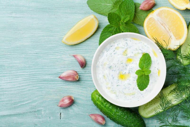 Tzatziki tradicional do molho do iogurte grego com ingredientes pepino, hortelã, aneto, limão e alho na opinião de tampo da mesa  fotos de stock royalty free