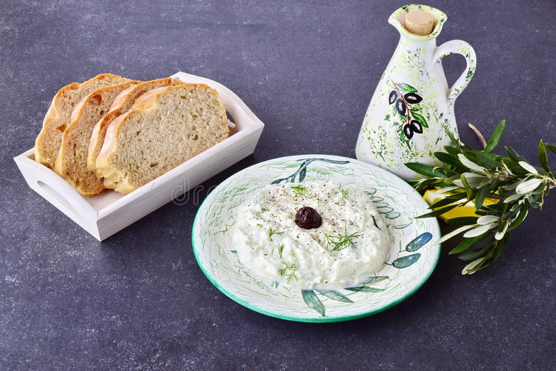 Tzatziki tradicional grego do molho com azeitonas, frasco do azeite, limão e pão em um fundo abstrato cinzento Saudável fotos de stock