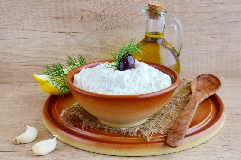 Tzatziki - yoghurtsås med gurkan, dill, olivolja, citronen och vitlök i en traditionell bunke, traditionell grek arkivbild