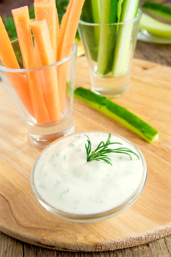 Tzatziki yogurt dip (sauce). Fresh Greek Tzatziki yogurt dip (sauce) and assorted vegetables on wooden table royalty free stock photography