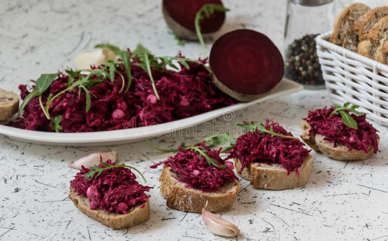 Tzatziky from red beet and cottage cheese. Decorated with fresh arugula royalty free stock photos