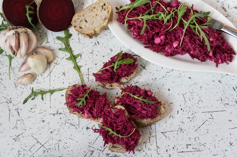 Tzatziky from red beet and cottage cheese. Decorated with fresh arugula stock image