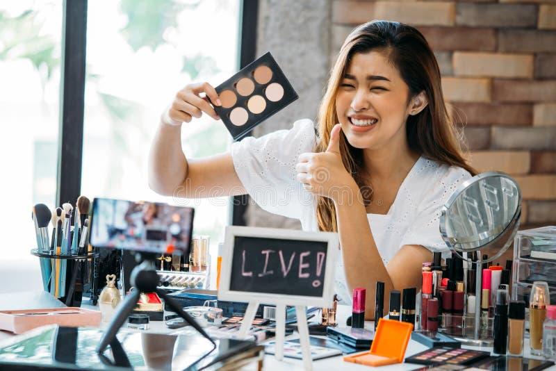 Uśmiechnięci Azjatyccy kobiety mienia eyeshadows i seansu kciuk w górę zdjęcia royalty free