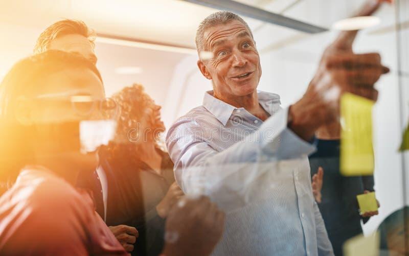 Uśmiechnięci biznesmeni brainstorming z kij notatkami w offi zdjęcie royalty free