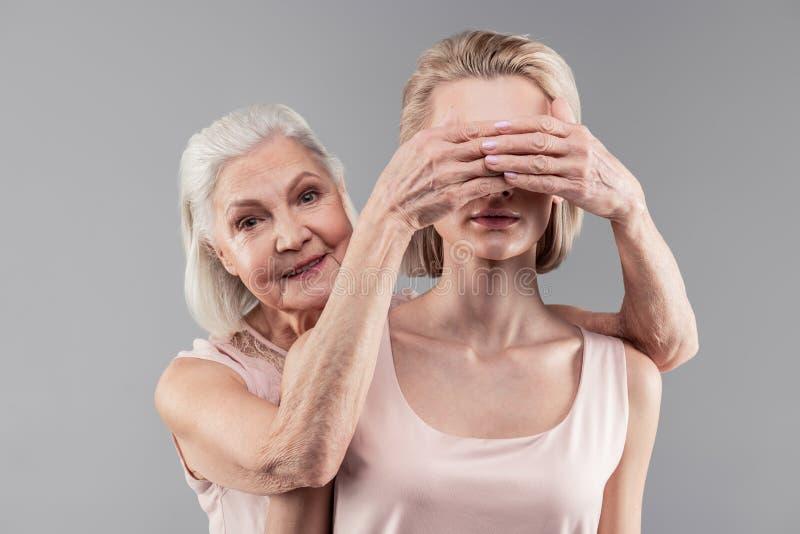 Uśmiechnięci przyjemni starszy kobiety nakrycia oczy jej piękna córka zdjęcie royalty free