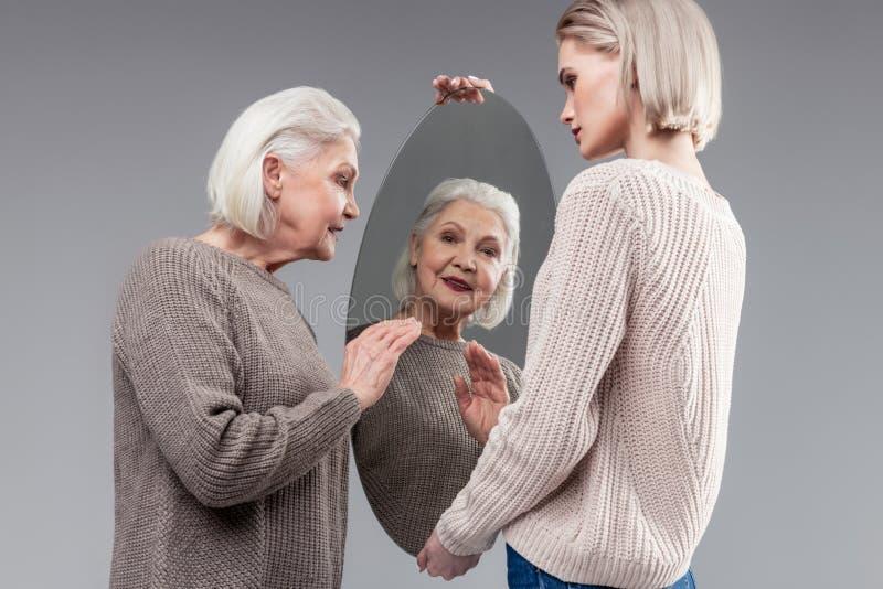 Uśmiechnięta atrakcyjna starsza dama w popielatym trykotowym pulowerze sprawdza jej pojawienie obrazy stock