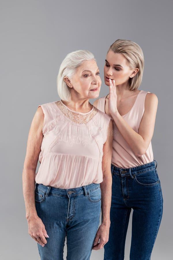 Uśmiechnięta baczna stara kobieta słucha znacząco plotkuje zdjęcie stock