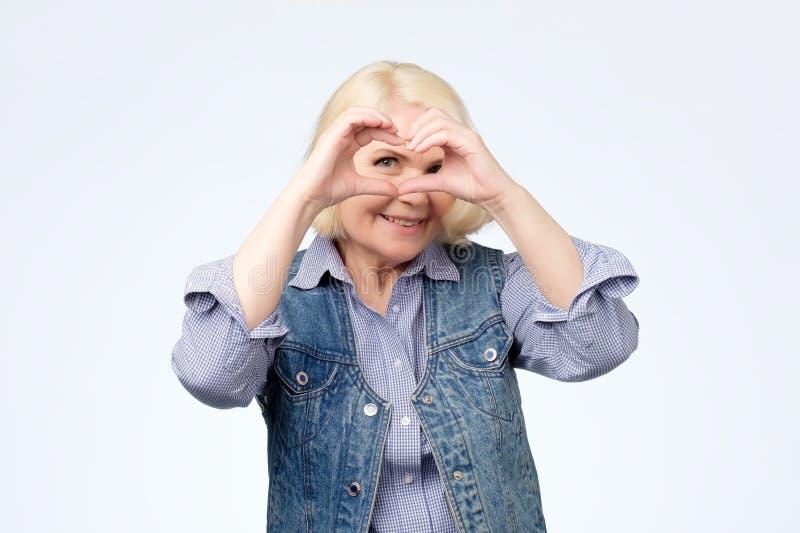 Uśmiechnięta blondynki kobieta, dziewczyna pokazuje serce znakowi z pomocą ona ręki obraz stock