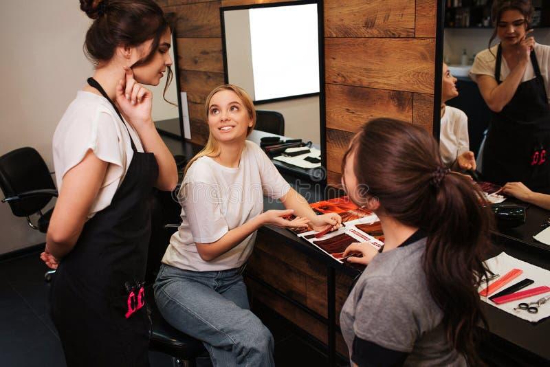 Uśmiechnięta blondynki młoda kobieta pokazuje włosianego kolor od palety jej fryzjer przed barwić w piękno salonie piękno obrazy stock