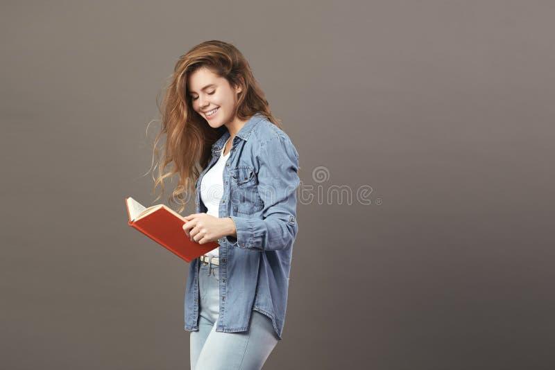 Uśmiechnięta brązowowłosa dziewczyna ubierająca w białej koszulce, cajgach i cajgach, czyta książkę na szarym tle obrazy stock