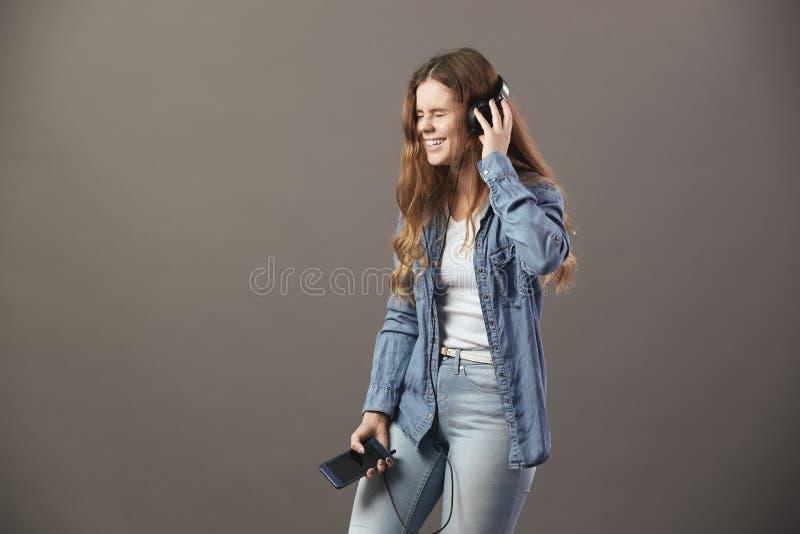 Uśmiechnięta brązowowłosa dziewczyna ubierająca w białej koszulce, cajgi i cajgów koszulowi chwyty, dzwonimy w jej ręce i słucham zdjęcia stock