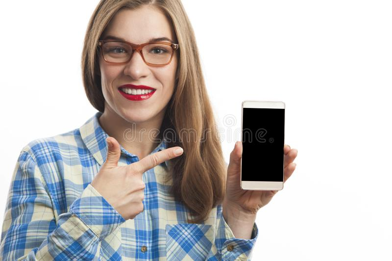 Uśmiechnięta caucasian kobieta w szkockiej kraty koszula mienia smartphone zdjęcie royalty free