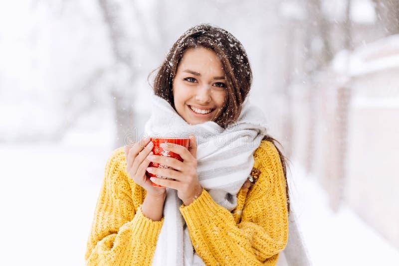 Uśmiechnięta ciemnowłosa dziewczyna w żółtym pulowerze, cajgach i białej szalik pozycji z czerwonym kubkiem na śnieżnej ulicie na obrazy royalty free
