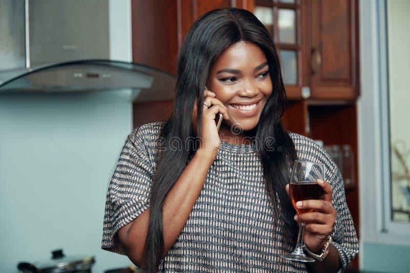 Uśmiechnięta kobieta z wineglass mówieniem na telefonie zdjęcie stock