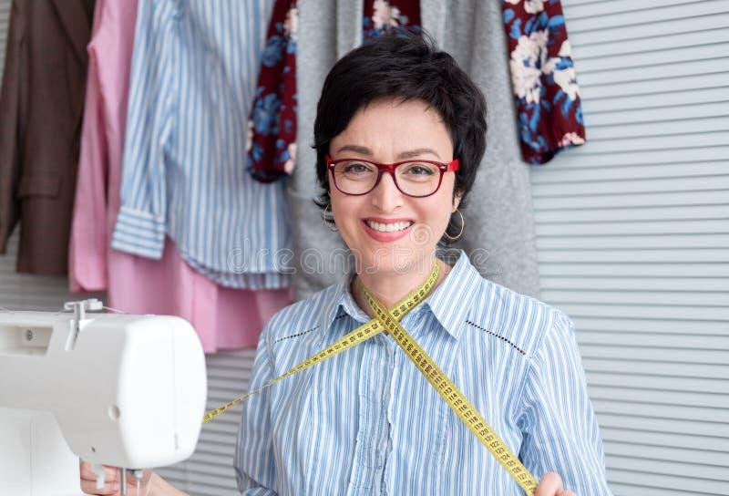 Uśmiechnięta krawcowa w eyeglasses pracuje przy krawczyny sklepem z elektryczną przemysłową szwalną maszyną zdjęcie stock