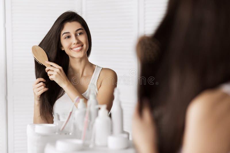 Uśmiechnięta młoda kobieta brashing jej włosy fotografia stock
