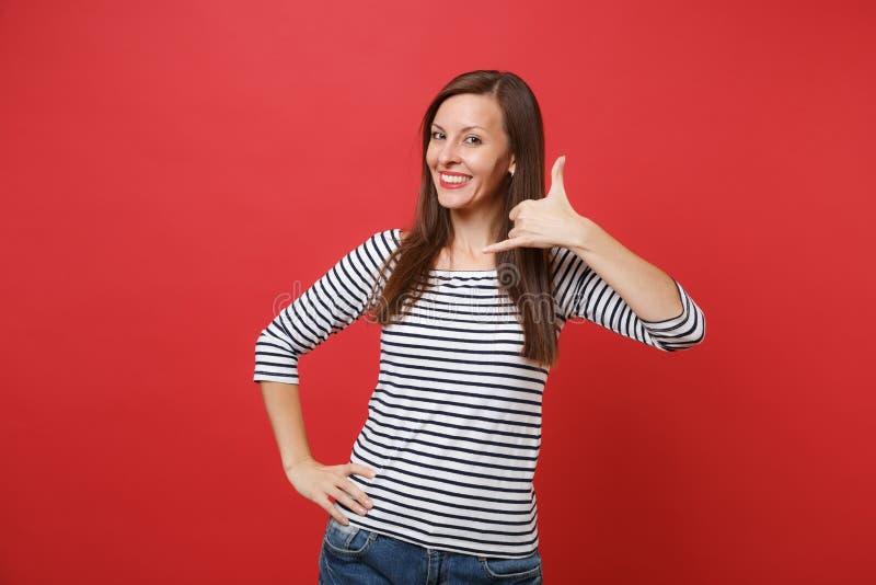 Uśmiechnięta młoda kobieta robi telefonu gestowi jak mówi: dzwoni ja z powrotem z ręką, palce jak opowiadać na telefonie obrazy stock