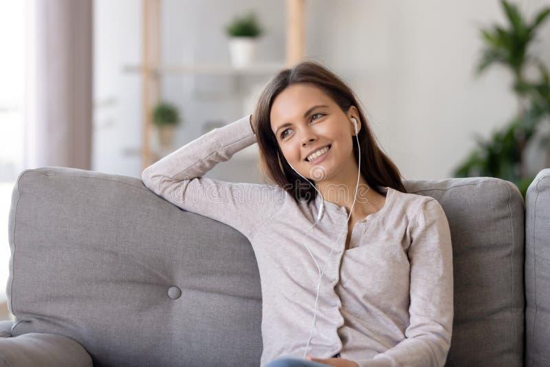 Uśmiechnięta młoda kobieta w słuchawkach, słucha ulubiona muzyka zdjęcia stock