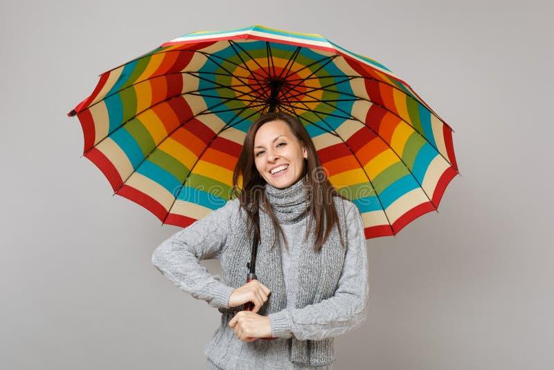 Uśmiechnięta młoda kobieta w szarym pulowerze, szalik trzyma kolorowego parasol odizolowywający na popielatym tle w studiu Zdrowy obrazy royalty free
