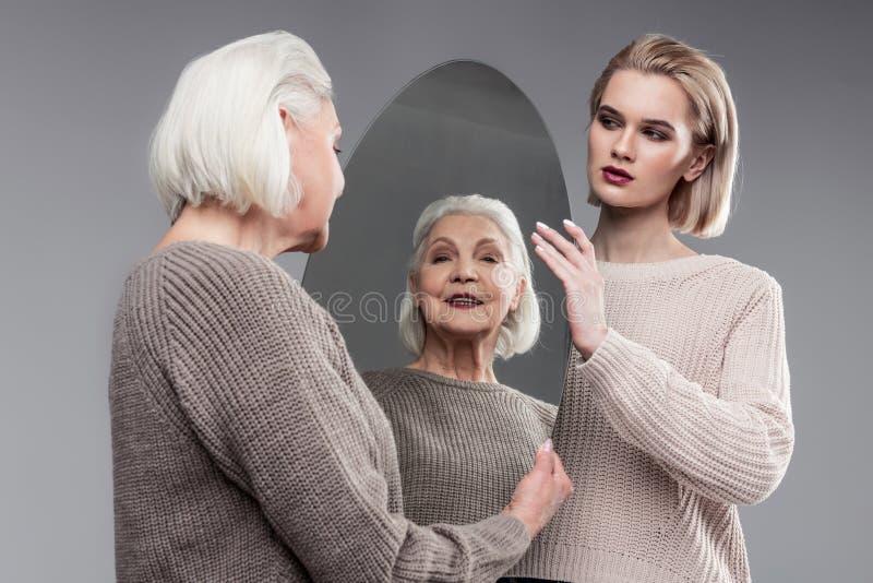 Uśmiechnięta siwowłosa starsza kobieta cieszy się jej pojawienie w lustrzanym odbiciu zdjęcia royalty free