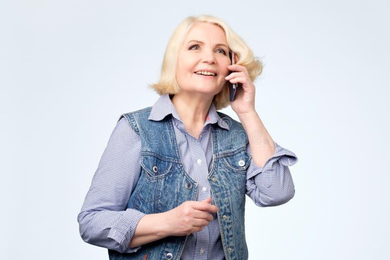 Uśmiechnięta starsza blondynki kobieta opowiada na telefonie zdjęcie stock