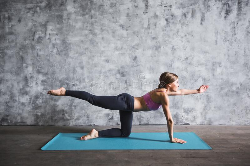 Uśmiechniętej pięknej kobiety ćwiczy joga, siedzi na joga macie w gym obrazy royalty free