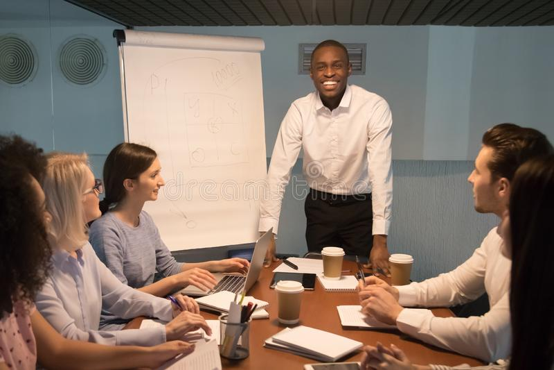 Uśmiechnięty afrykanina trenera lider patrzeje kamerę przy drużynowym spotkaniem zdjęcia stock