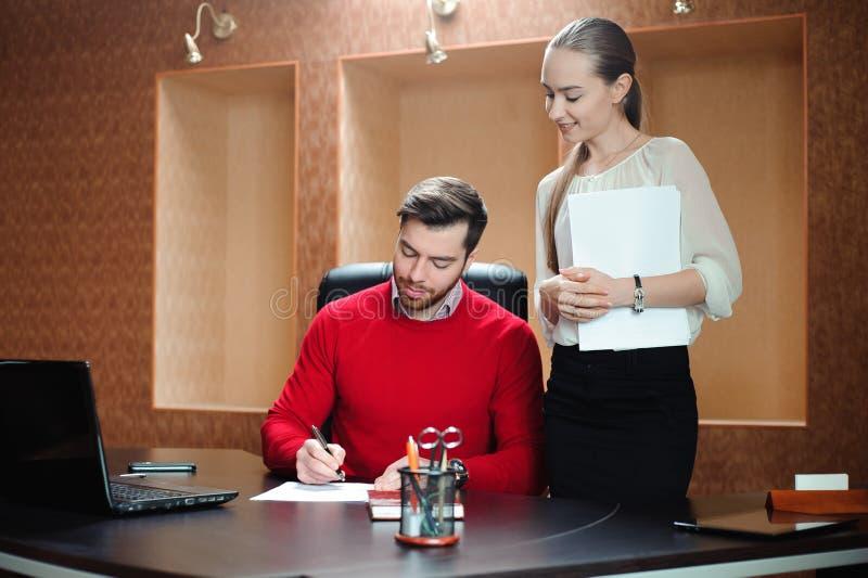 Uśmiechnięty biznesowy specjalista i sekretarka pracuje w nowożytnym biurze obraz royalty free