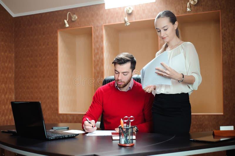 Uśmiechnięty biznesowy specjalista i sekretarka pracuje w nowożytnym biurze obrazy royalty free
