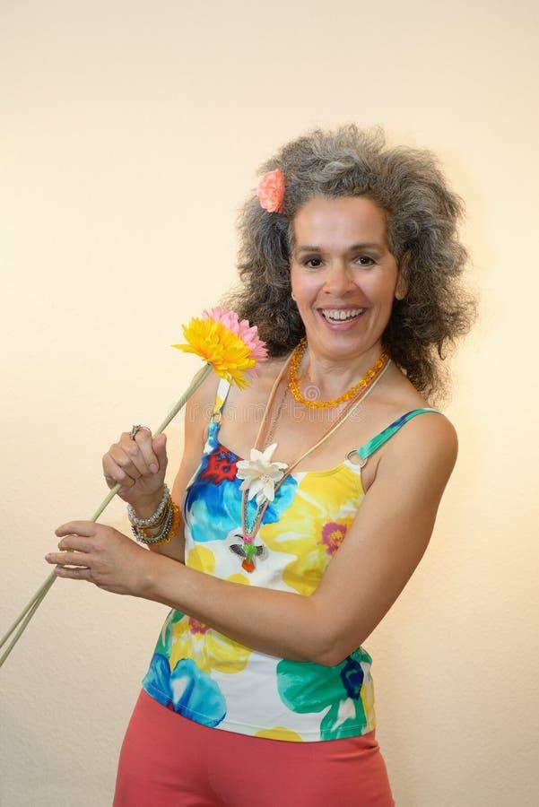 Uśmiechnięty dojrzały kobiety mienie kwitnie lato strój obrazy royalty free