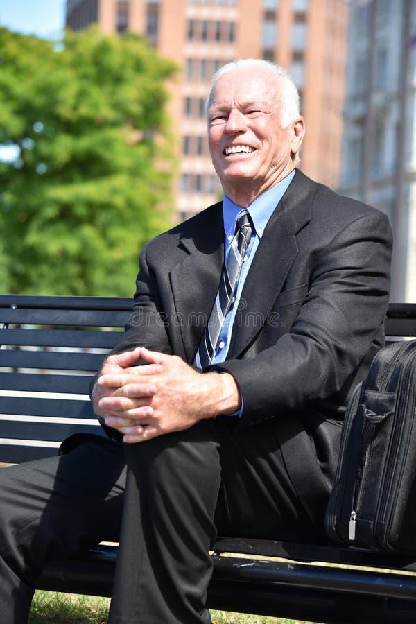 Uśmiechnięty Dorosły Starszy Biznesowy mężczyzna Jest ubranym kostiumu I krawata obsiadanie Na ławce obrazy stock