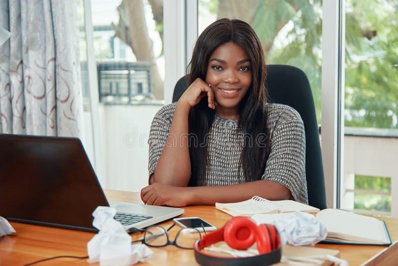 Uśmiechnięty etniczny bizneswoman przy pracującym stołem obrazy stock