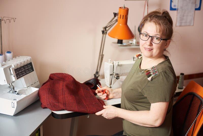 Uśmiechnięty kobieta krawczyna na szwalnym procesie spódnica, trzyma nożyce Overlock i maszyna na tle Boczny widok fotografia stock