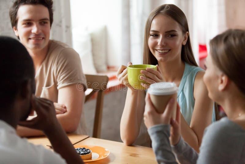 Uśmiechnięty kobiety słuchanie opowiada przyjaciela przy spotkaniem w kawiarni obraz stock