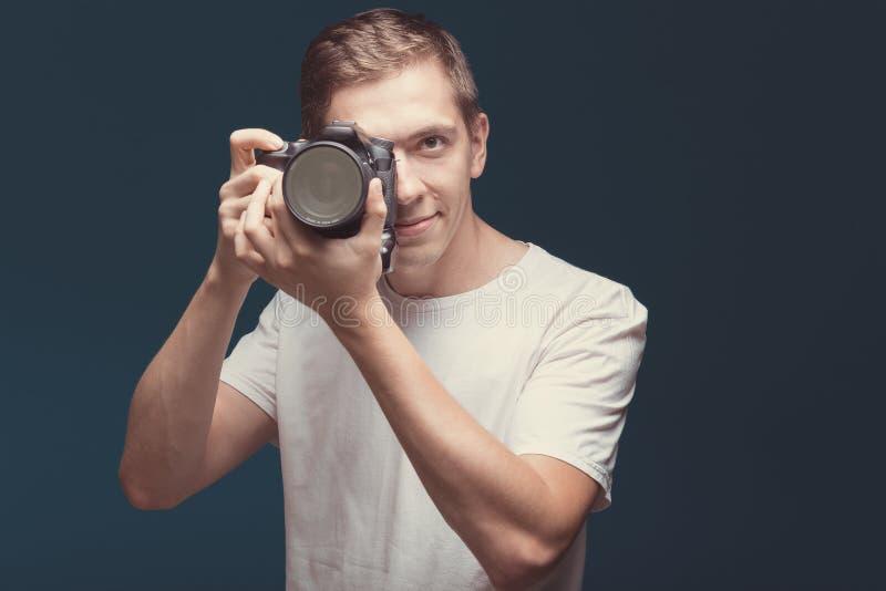 Uśmiechnięty mężczyzna z kamerą odizolowywającą na ciemnym tle Młody człowiek trzyma cyfrową kamerę i robi fotografii patrzeje na zdjęcia royalty free