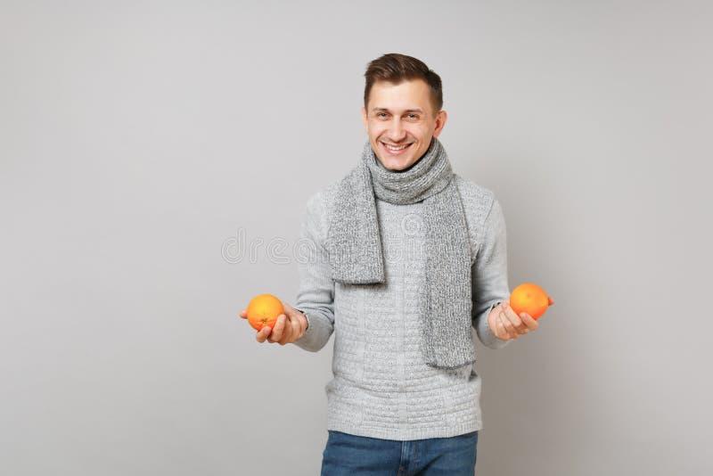 Uśmiechnięty młody człowiek w szarym pulowerze, szalika mienia pomarańcze na popielatym ściennym tle, pracowniany portret Zdrowy zdjęcia stock