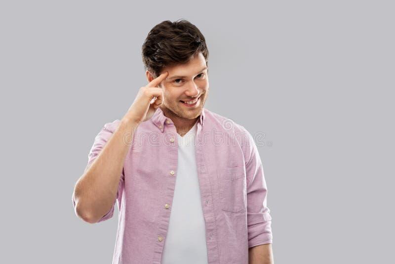 Uśmiechnięty młody człowiek wskazuje palec jego głowa obraz royalty free
