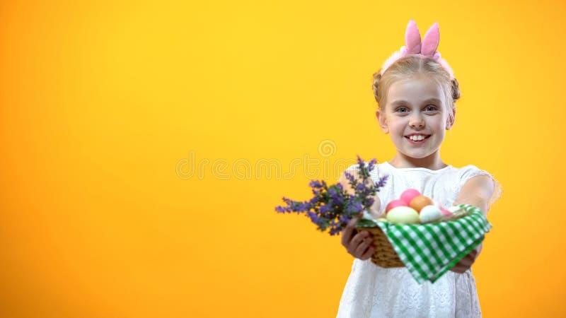 Uśmiechnięty małe dziecko pokazuje kosz z kolorowych jajek żółtym tłem, wielkanoc obrazy royalty free