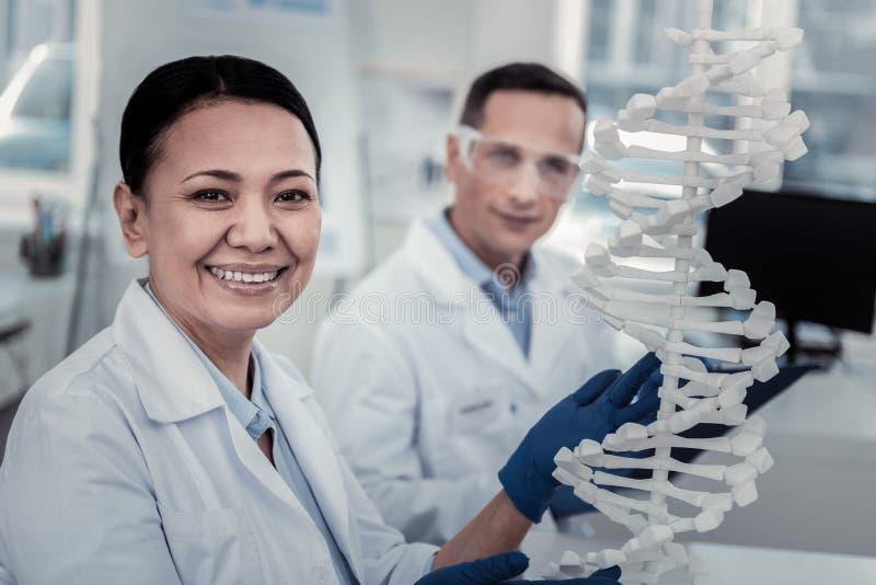 Uśmiechnięty naukowiec próbuje odszyfrowywać DNA sekrety obraz stock