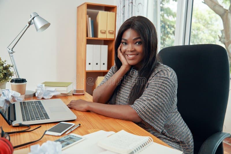Uśmiechnięty nowożytny bizneswoman przy stołem w biurze obraz stock