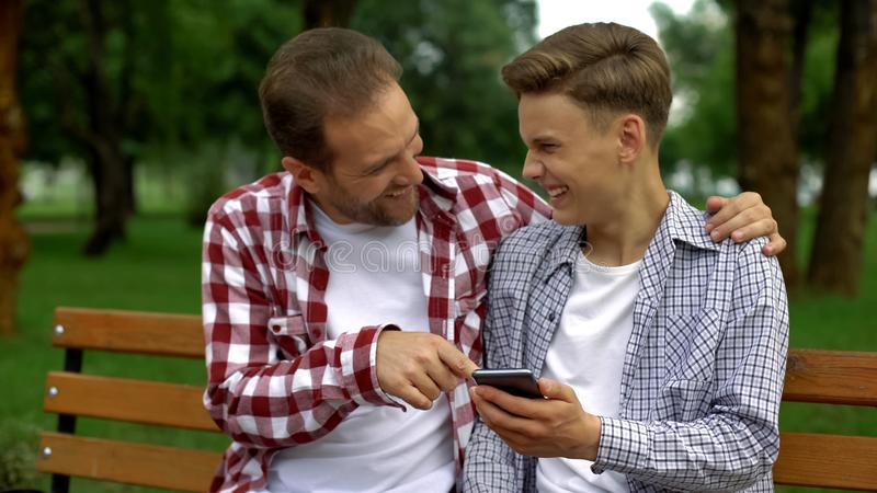Uśmiechnięty ojciec i syn śmia się przy śmieszną fotografią krewny na smartphone, odpoczynek fotografia royalty free
