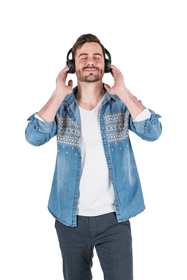 Uśmiechnięty przypadkowy mężczyzna słucha muzyka, odizolowywająca zdjęcia royalty free