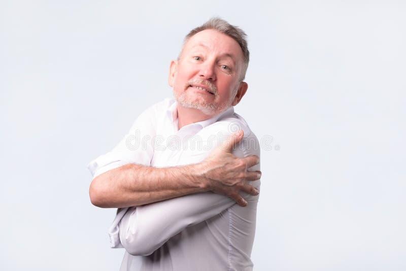 Uśmiechnięty starszego mężczyzny mienia przytulenie himself na popielatym ściennym tle obrazy royalty free
