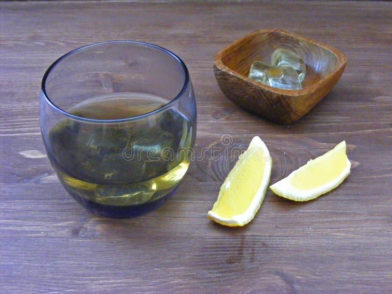 Uísque alcoólico Bourbon em um vidro com gelo, vidro do conhaque com limão fotografia de stock royalty free