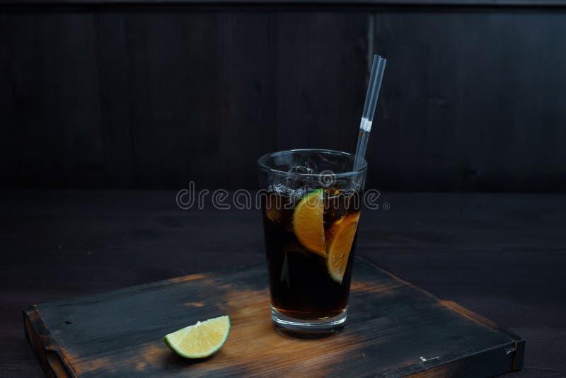 Uísque com coca-cola com gelo e fatias de cal fresco em uma tabela de madeira na barra fotografia de stock royalty free